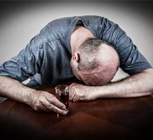 Alcoholic man face down on table with a shot of whiskey in his hand.